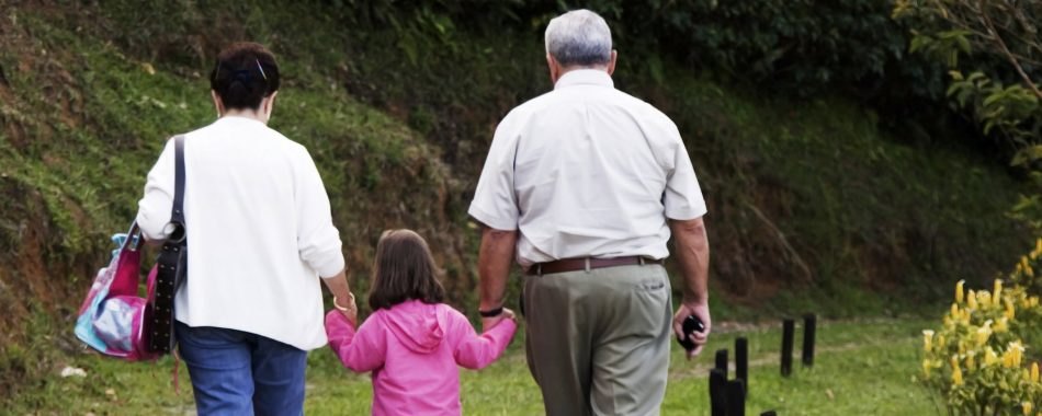 grandparents holding hands with child, walking away from camera