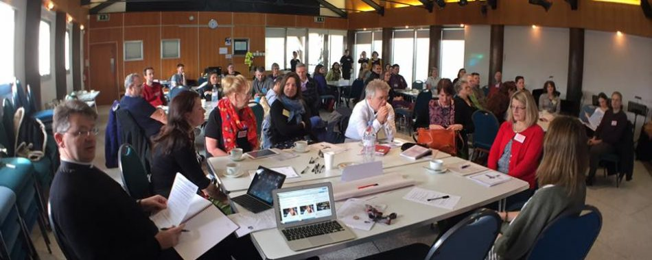 lots of people sat at tables at a workshop event
