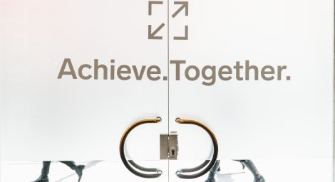 People walking past a door etched with Achieve Together