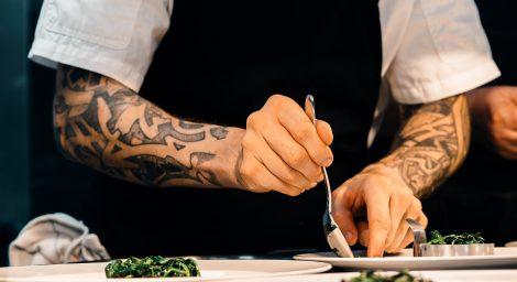 Photo of man with tattoos working in restaurant kitchen